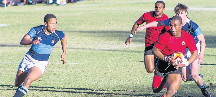 BREAKING THE LINE: Kingswood College first rugby team smashed the St Andrew's College boys last week in their first victory on home ground since 1962 during last week's K-Day sports festival.