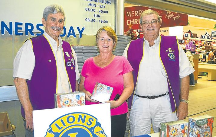 LION HEARTS: Mike Newlands, left, sold Susan Hunt, centre, a Lions Christmas cake at the Heritage Mall on Tuesday. Overlooking proceedings was Norman Elliott. Picture: ROB KNOWLES