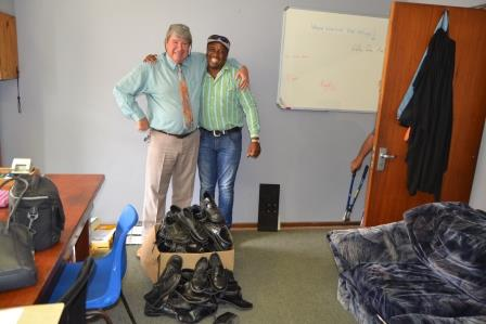 SHOE-IN: Thirty-six pairs of good quality shoes were handed over to Tele, right, at the school on Tuesday, pictured here with deputy principal Roger Nock (left)
